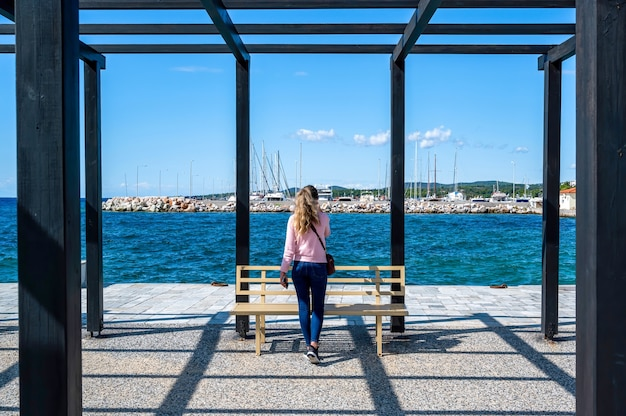 Une femme parlant au téléphone dans un gazebo sur une jetée avec des poteaux en métal noir et un banc, la mer égée à nikiti, grèce