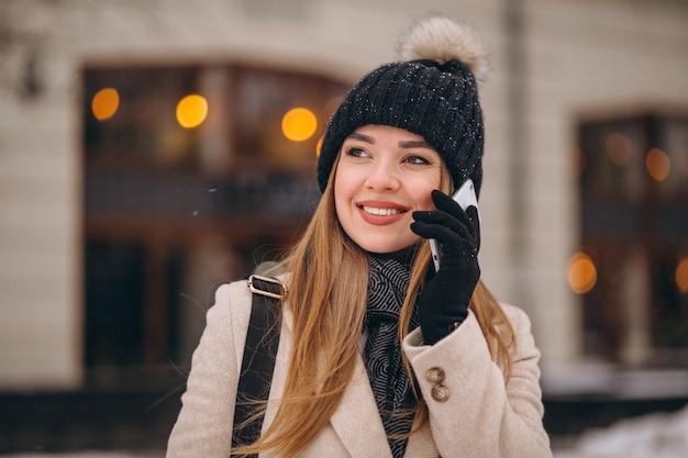 Femme parlant au téléphone à l'extérieur du café
