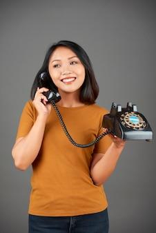 Femme parlant au téléphone filaire rétro