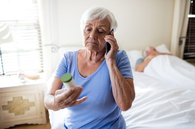 Femme Parlant Au Téléphone Mobile Et Tenant Une Bouteille De Prescription De Médicaments Dans La Chambre à Coucher à La Maison Photo Premium