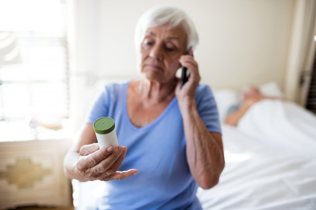 Femme parlant au téléphone mobile et tenant une bouteille de prescription de médicaments dans la chambre à coucher à la maison