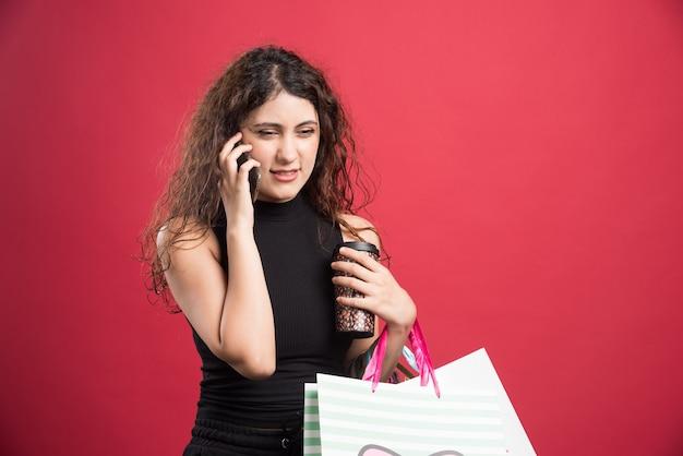 Femme parlant au téléphone avec tasse et sacs sur fond rouge. photo de haute qualité