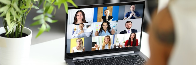 Femme parlant avec des collègues internationaux à l'aide du service de chat vidéo en ligne sur le lieu de travail