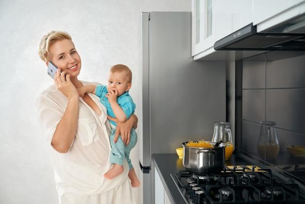 Femme parlant sur plat de cuisson mobile et transportant bébé