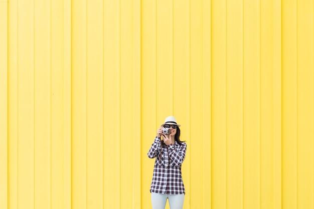 Femme parlant un selfie avec un appareil photo vintage sur fond jaune