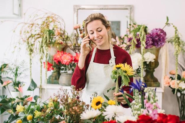 Femme parlant sur smartphone dans un magasin de fleurs