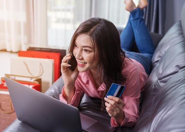 Femme parlant sur smartphone pour faire des achats en ligne avec carte de crédit dans le salon
