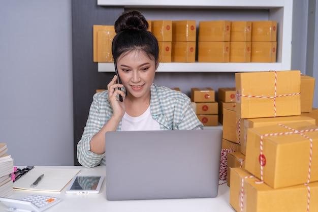 Femme parlant sur un smartphone et utilisant un ordinateur portable pour vendre des produits en ligne depuis le bureau à domicile