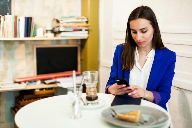 La femme parle au téléphone assis dans le café
