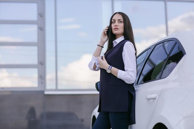 Une femme parle au téléphone avec une voiture blanche