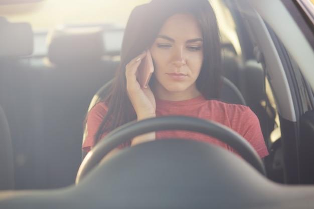 Une femme parle par téléphone portable avec son mari, ne sait pas quoi faire comme arrêts sur la route, n'a pas d'essence dans l'automobile