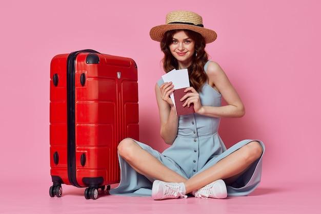 Femme avec passeport et billet d'avion valise rouge vacances passager libre