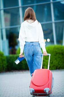 Femme avec passeport et billets près de l'aéroport