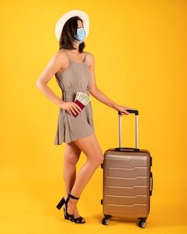 Femme avec passeport et valise, portant un masque