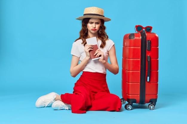 Femme avec passeport valise rouge et billets d'avion destination de vacances