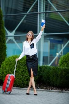 Une femme avec un passeport et une valise rouge près de l'aéroport part en voyage