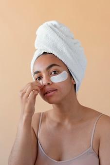Femme avec des patchs oculaires et une serviette