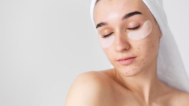 Femme avec des patchs oculaires et les yeux fermés