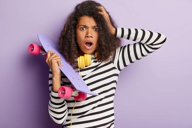 Femme patineuse choquée posant avec une longue planche