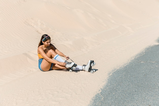 Femme avec des patins assis sur le sable