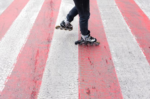 Femme en patins à roues alignées sur le passage pour piétons