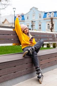 Femme avec patins à roues alignées s'amusant sur un banc