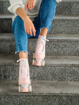 Femme avec des patins à roulettes posant dans les escaliers