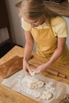 Femme pâtissière ou boulanger ou femme au foyer pétrit la pâte dans la cuisine. publicité de produits de boulangerie maison