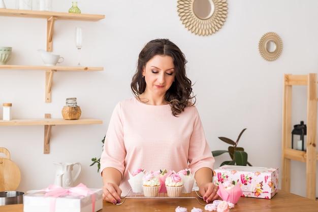 Une femme pâtissière à la maison dans la cuisine préparait des cupcakes. petits gâteaux faits maison avec de la crème