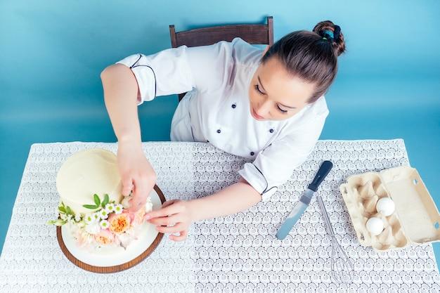 Une femme pâtissière pâtissière décore un gâteau d'anniversaire blanc crème à deux niveaux (mariage) avec des fleurs fraîches sur une table en studio sur fond bleu