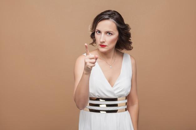 Femme de patron avec un visage sérieux pointant le doigt d'avertissement à la caméra. femme exprimant ses émotions en robe blanche, lèvres rouges et coiffure frisée foncée. intérieur, isolé sur fond beige ou marron clair