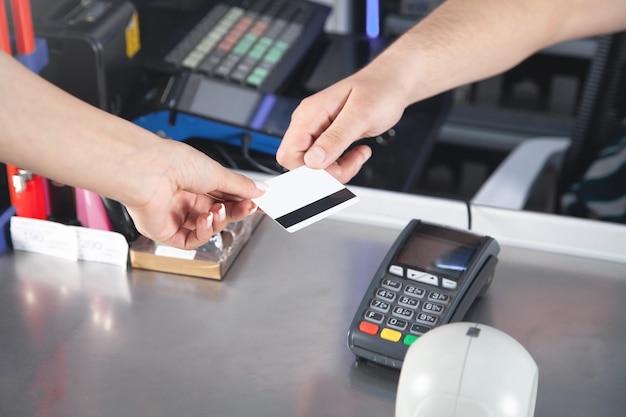 Femme payant avec carte de crédit au supermarché.