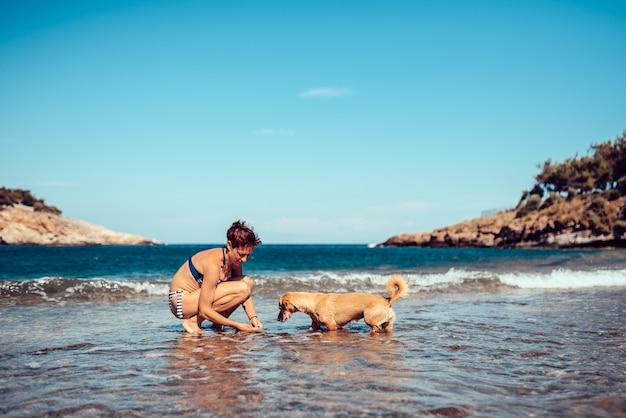Femme payant avec un chien sur la plage