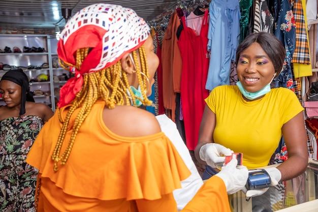 Femme payant avec sa carte de crédit dans une boutique locale