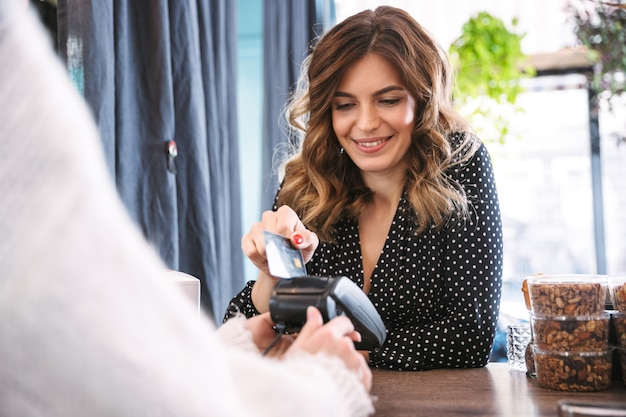 Femme de payer avec une carte de débit dans un restaurant, serveuse tenant un terminal de paiement