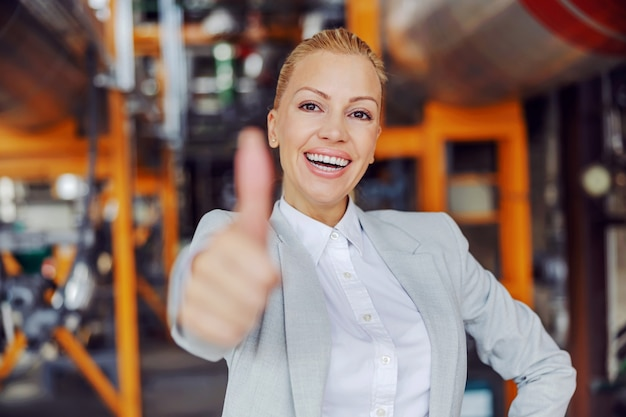 Femme pdg indépendante d'âge moyen en costume debout dans une installation de chauffage et montrant les pouces vers le haut et regardant la caméra.