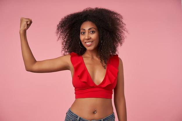Femme à la peau foncée assez bouclée positive avec piercing au nombril avec un large sourire joyeux, démontrant son pouvoir dans la main levée, posant sur rose