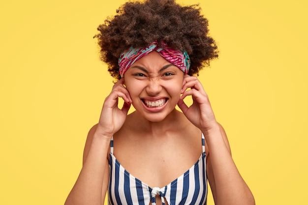 Une femme à la peau foncée assez mécontente se bouche les oreilles, agacée par un bruit terrible, exige le silence et une atmosphère calme, serre les dents