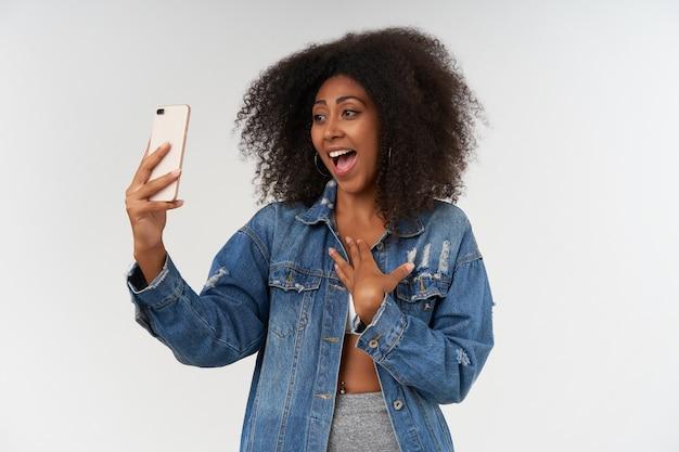 Une femme à la peau foncée et bouclée ravie avec un haut décontracté en blanc et un manteau en jean gardant la paume sur sa poitrine tout en ayant un appel vidéo avec son amie, entendant de bonnes nouvelles inattendues, posant sur un mur blanc