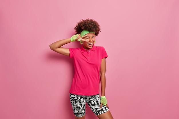 Une femme à la peau foncée heureuse et ludique cligne des yeux et des gestes signe v a une humeur folle