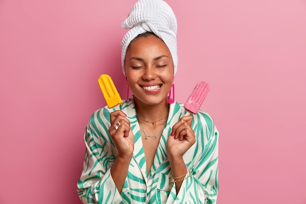 Une femme à la peau foncée heureuse mord les lèvres, détient une délicieuse crème glacée appétissante, imagine un goût agréable de dessert glacé, porte une serviette enveloppée sur la tête, habillée en robe,