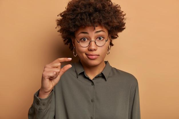 Une femme à la peau foncée, mécontente et perplexe, façonne un objet de petite taille, confuse par quelque chose de très petit, sourit narquoisement, porte des lunettes optiques et une chemise, explique et mesure avec les doigts, se tient à l'intérieur