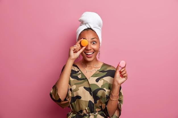 Femme à la peau foncée positive détient de savoureux macarons