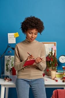 Une femme à la peau foncée se tient à l'intérieur, porte un col roulé et un jean, écrit des notes dans le journal avec un crayon