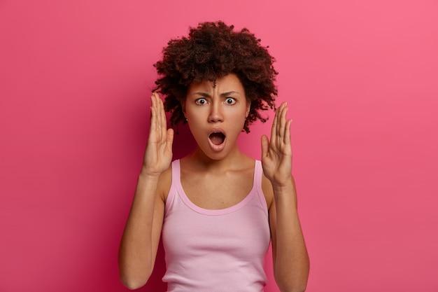 Une femme à la peau foncée surprise fait un grand signe de la main, montre la largeur du paquet, a une expression choquée, s'habille avec désinvolture, pose sur un mur rose, fait des gestes et mesure quelque chose de très énorme