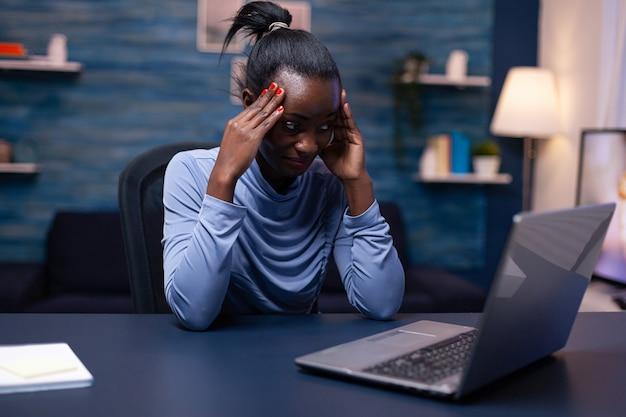 Femme à la peau foncée touchant le front à cause de maux de tête en travaillant à domicile. employé concentré fatigué utilisant le réseau de technologie moderne sans fil faisant des heures supplémentaires.