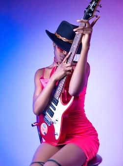 La femme à la peau foncée vêtue d'une robe courte rose et d'un chapeau avec une guitare électrique