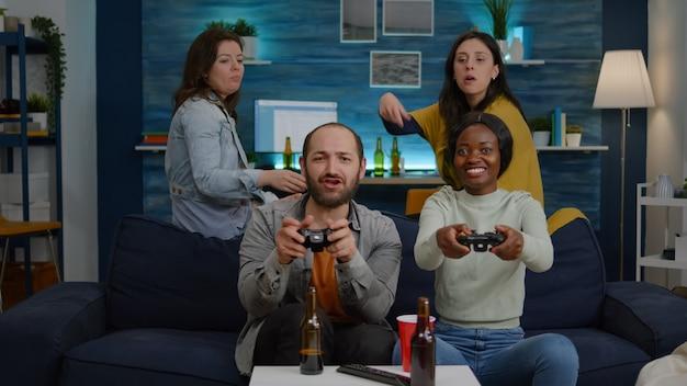 Femme à la peau noire jouant à des jeux vidéo en ligne contre des amis de l'homme