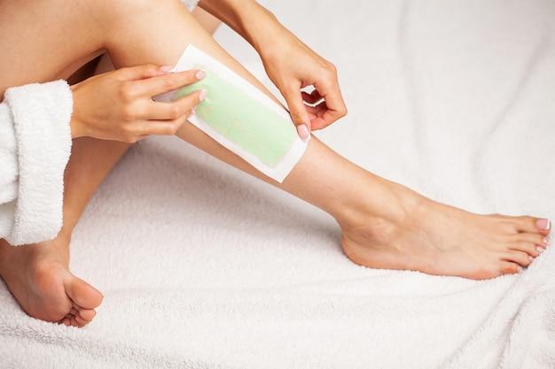 Femme avec une peau parfaite sur ses pieds applique du ruban de cire sur sa jambe pour enlever les poils