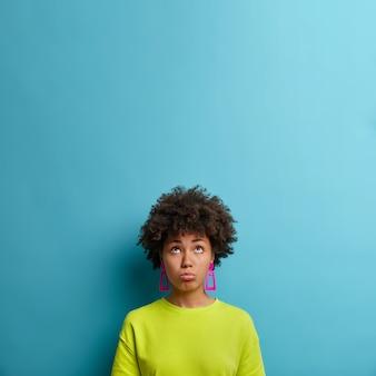 Une femme à la peau sombre bouleversée regrettable regarde avec une expression triste et frustrée ci-dessus, mécontente des problèmes, porte un t-shirt vert et des boucles d'oreilles, mur bleu avec un espace vide vide